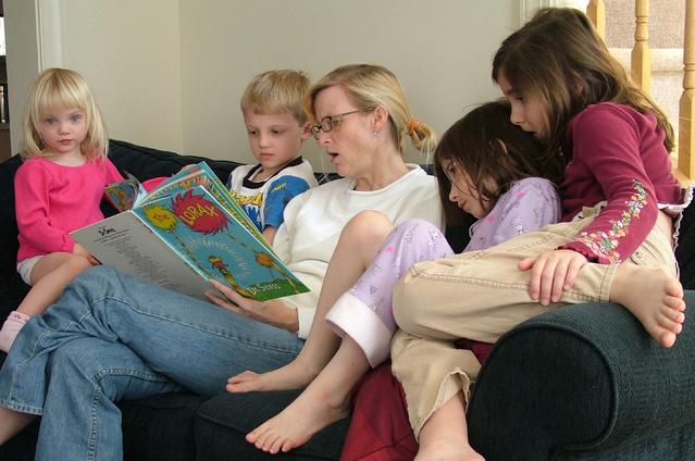 děti na sedací soupravě při čtení pohádky
